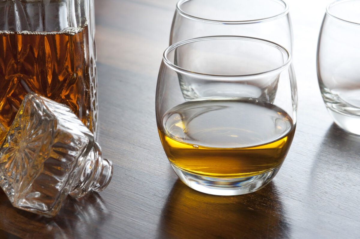 Glass of scotch whiskey alongside an open decanter on a bar counter or table with additional empty glasses