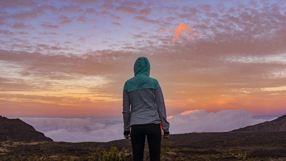 young woman standing on mountains look at clouds