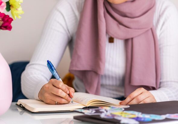 woman sits at table making notes in journal